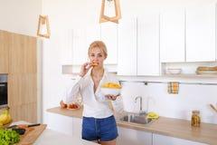 La muchacha bonita que presenta y come las patatas fritas, se coloca en el centro de ki Imágenes de archivo libres de regalías