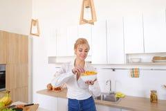 La muchacha bonita que presenta y come las patatas fritas, se coloca en el centro de ki Fotos de archivo libres de regalías