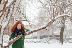 La muchacha bonita se aferra en el árbol al aire libre en el día de invierno Fotografía de archivo libre de regalías