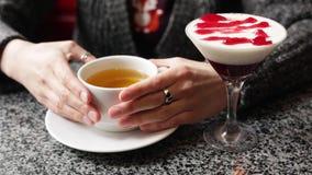 La muchacha bonita se calienta las manos, sosteniendo una taza de té negro o verde caliente almacen de metraje de vídeo
