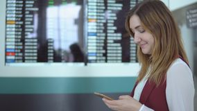 La muchacha bonita se coloca en el fondo del marcador borroso con el vuelo del aviso y de la opción en el smartphone almacen de video