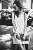 La muchacha bonita se está colocando cerca de un coche Fotografía de archivo libre de regalías