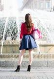 La muchacha bonita se está colocando delante de una fuente Imagen de archivo