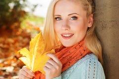 La muchacha bonita se está sentando en parque del otoño con el arce Imagen de archivo
