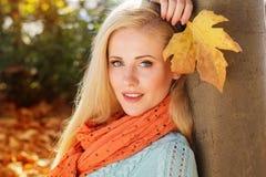 La muchacha bonita se está sentando en parque del otoño con el arce Fotos de archivo