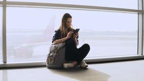 La muchacha bonita se sienta con el teléfono por la ventana terminal Pasajero femenino europeo con la mochila que mecanografía y  almacen de metraje de vídeo