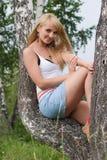 La muchacha bonita se sienta en abedul. Fotos de archivo libres de regalías