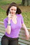 La muchacha bonita se sienta en el teléfono celular del banco de parque que habla imágenes de archivo libres de regalías