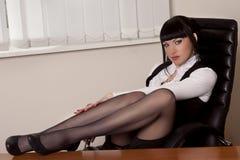 La muchacha bonita se sienta en las piernas de la tabla en la oficina foto de archivo libre de regalías