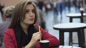 La muchacha bonita se sienta en un café de la calle con la bebida y sonrisas en la cámara metrajes