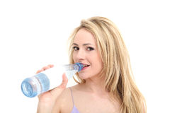 La muchacha bonita sonríe mientras que ella bebe de una botella Fotos de archivo libres de regalías