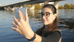La muchacha bonita toma imágenes de sí misma contra la perspectiva del río Selfies cerca del agua Primer lento almacen de metraje de vídeo