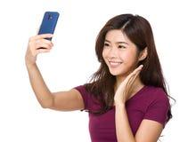 La muchacha bonita toma un autorretrato con su teléfono elegante Fotos de archivo libres de regalías
