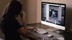 La muchacha bonita trabaja en el ordenador y una tableta metrajes