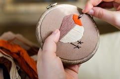 La muchacha borda un pájaro con una puntada Concepto de DIY, aficiones, creatividad, ropa y decoración interior Foto de archivo libre de regalías