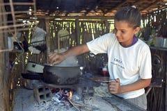La muchacha brasileña está cocinando en un fuego de madera con leña Imagenes de archivo