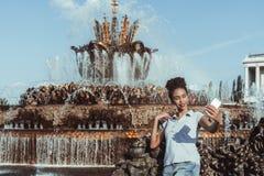 La muchacha brasileña está tomando el selfie al lado de la fuente usando el teléfono móvil Fotos de archivo