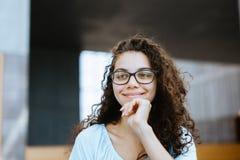 La muchacha brasileña linda con el pelo rizado que escucha una conversación y tiene una idea foto de archivo libre de regalías