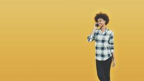 La muchacha brasileña rizada está hablando en el teléfono Fotografía de archivo
