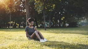 La muchacha brasileña se está sentando en el parque, usando el teléfono móvil Imagenes de archivo