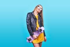 La muchacha bronceada atractiva con sonrisa en cara lleva la chaqueta de cuero negra que presenta con placer Foto interior de la  Fotos de archivo libres de regalías