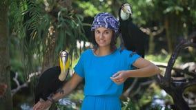 La muchacha bronceada en un vestido azul y una bufanda en su cabeza está en la selva tropical, e intenta hablar con los loros, te metrajes