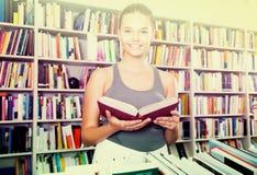 La muchacha Brunete del adolescente busca el libro derecho en biblioteca Fotografía de archivo libre de regalías