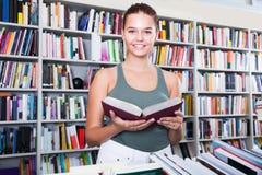 La muchacha Brunete del adolescente busca el libro derecho en biblioteca Fotos de archivo