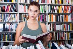 La muchacha Brunete del adolescente busca el libro derecho en biblioteca Imagen de archivo