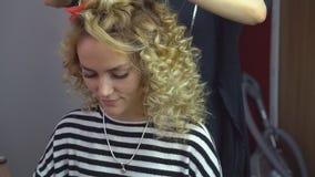 La muchacha cabelluda hermosa, rubia con el pelo largo, peluquero hace rizos africanos en un salón de belleza Cuidado del cabello almacen de metraje de vídeo