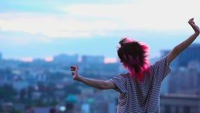La muchacha cabelluda rosada goza de la libertad y del viento, top del edificio de la ciudad, vida del tejado de la paz almacen de metraje de vídeo