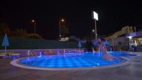 La muchacha cae en la ropa en la piscina en el hotel después del partido metrajes