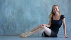 La muchacha calienta en el estudio de la escuela del ballet La muchacha hermosa de pelo rubio sonríe delante de la cámara Los jóv almacen de metraje de vídeo