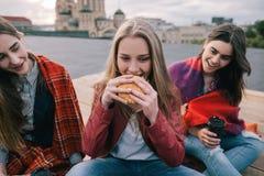 La muchacha caliente-observada los jóvenes come la hamburguesa Imagen de archivo