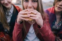 La muchacha caliente-observada los jóvenes come la hamburguesa, cierre para arriba Foto de archivo