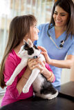 La muchacha calma abajo su gato enfermo en clínica veterinaria Imagen de archivo libre de regalías