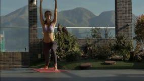 La muchacha cambia actitudes de la yoga en terraza del tejado bajo luz del sol