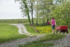 La muchacha camina abajo de carril de la primavera con la flor y los carros Imagenes de archivo
