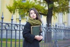 La muchacha camina abajo de la calle con un libro Fotografía de archivo libre de regalías