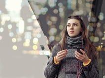 La muchacha camina abajo de la calle de la ciudad que sostiene un smartphone Fotografía de archivo