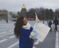 La muchacha camina alrededor de la ciudad con el mapa Imagenes de archivo