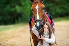 La muchacha camina con su caballo querido Imagenes de archivo