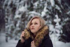 La muchacha camina en el bosque del invierno Foto de archivo