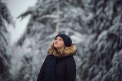 La muchacha camina en el bosque del invierno Fotos de archivo