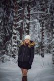 La muchacha camina en el bosque del invierno Imagenes de archivo