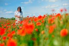 La muchacha camina en el campo de la amapola imagen de archivo libre de regalías