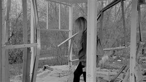 La muchacha camina en el marco de un edificio abandonado quebrado viejo La atmósfera de la desolación y de la devastación Plan ci almacen de video