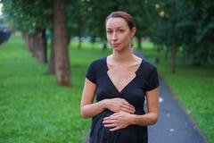 La muchacha camina en el parque de la tarde Imagen de archivo libre de regalías