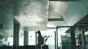La muchacha camina en el salón del aeropuerto almacen de metraje de vídeo