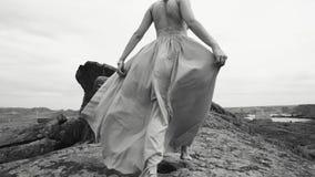 La muchacha camina las piedras descalzo, sosteniendo el vestido almacen de metraje de vídeo